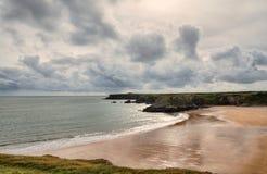 Bred tillflyktsort, Pembrokeshire, under en stormig sky. royaltyfria foton