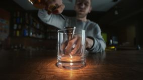 Bred vinkelmakrovideo av hällande whisky till exponeringsglaset i slowmotion hällande alkohol i en stång, bartender på arbete arkivfilmer