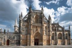 Bred vinkelsikt av den medeltida Batalha för främre ingång kloster Portugal royaltyfri foto