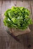 Breda smör på grönsallat på en säckvävtorkduk över lantlig bakgrund Royaltyfria Foton