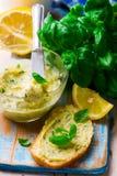 Breda smör på med en basilika och en citron för smörgåsar arkivbild