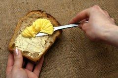 breda smör på på fördelande rostat bröd royaltyfri bild