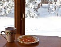 Breda smör på smoothered kräppar med den röda kaviaren och koppen av varmt te på trätabellen Snö utanför royaltyfri foto