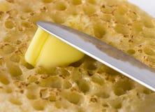 bredd smör på crumpet Arkivbild