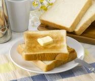bredd smör på rostat bröd arkivbild