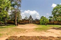 Brede de hoek buitenmuur en toren van Banteaysamre in bomen open grond royalty-vrije stock fotografie