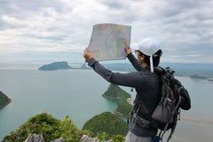 Brede hoek die van de hipster jonge Aziatische mens wordt geschoten met rugzak die zich op de steen bevinden en kaart op de berg  stock fotografie