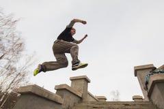 Brede hoekmening - parkour springend in het park van de de wintersneeuw - free-run opleiding royalty-vrije stock foto