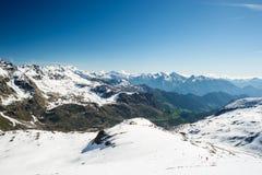 Brede hoekmening van een skitoevlucht in de afstand met elegante bergpieken die van de alpiene boog in wintertijd het gevolg zijn stock foto