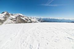 Brede hoekmening van een skitoevlucht in de afstand met elegante bergpieken die van de alpiene boog in wintertijd het gevolg zijn stock foto's
