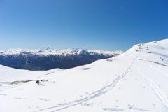 Brede hoekmening van een skitoevlucht in de afstand met elegante bergpieken die van de alpiene boog in wintertijd het gevolg zijn royalty-vrije stock foto's