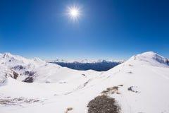 Brede hoekmening van een skitoevlucht in de afstand met elegante bergpieken die van de alpiene boog in wintertijd het gevolg zijn royalty-vrije stock afbeelding