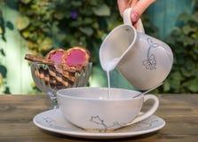 Brede kop op de lijst en thee met melk Stock Afbeelding