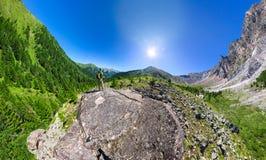 Brede luchtpanoramamens met rugzak die zich in bergen bevinden Royalty-vrije Stock Fotografie