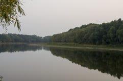 Brede rivier die over groene bosdaling stromen avond Bezinningen van bomen in het kalme water sundown royalty-vrije stock foto