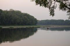 Brede rivier die over groene bosdaling stromen avond Bezinningen van bomen in het kalme water sundown royalty-vrije stock fotografie