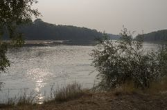 Brede rivier die over groene bosdaling stromen avond Bezinningen van bomen in het kalme water sundown royalty-vrije stock afbeelding