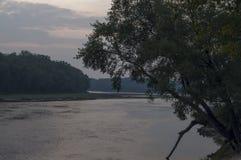 Brede rivier die over groene bosdaling stromen avond Bezinningen van bomen in het kalme water sundown stock foto's