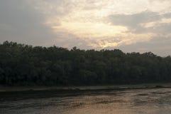 Brede rivier die over groene bosdaling stromen avond Bezinningen van bomen in het kalme water sundown stock foto