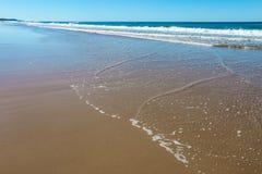 Brede uitgestrektheid van nat strand met water teruggaan en lage golven binnen en schuim die en water op het strand en de bezinni Royalty-vrije Stock Foto
