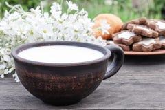 Bredvid kakorna och de vita blommorna ?r en kopp av mj?lkar p? en tr?tabell arkivbilder