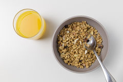 Breeakfast cereal bowl with orange juice. Healthy granola cereal in bowl stock photos