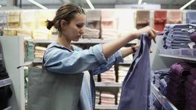 Breed assortiment van verschillende kleurenbadhanddoeken Zijaanzicht van een vrouwelijke koper tussen de rijen Opent de handdoeke stock video