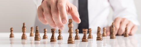 Breed bebouwd beeld van een zakenman in wit overhemd het spelen schaak royalty-vrije stock foto