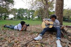 Breed hoekschot die van fotograaf een foto van de ontspannen jonge mens met hoofdtelefoons nemen die akoestische gitaar spelen en royalty-vrije stock afbeelding