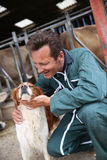 Breeder petting dog in front of the barn Royalty Free Stock Photography