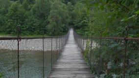 Breekbare houten brug over bergrivier, moed zich aan de andere kant te bewegen stock video