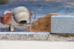 Breeze block wall construction with string line and cement mixer. And mortar royalty free stock photo
