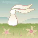 Breezy Bunny. White Bunny sits in the grass, long ears flapping in the breeze - a soft, vintage style Stock Illustration