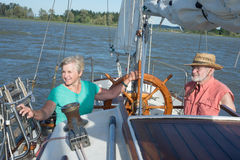 A Breezy Day. A happy senior couple enjoys time together sailing on a lake on a fine summer day royalty free stock images