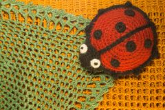 Breiend wolstuk speelgoed lieveheersbeestje op de achtergrond van de blamket kleurrijke textuur Royalty-vrije Stock Afbeeldingen