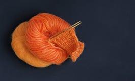 Breinaalden en oranje veelkleurige kleurrijke het garenbal van de mohair zachte warme winter op de donkere houten lijst Het begin Stock Afbeelding