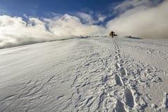 Breite Ansicht über den schneebedeckten Hügel mit Abdrücken und weit weg den Wanderer, der oben mit Rucksack in den Bergen geht Stockfotos