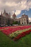 Breite Ansicht des Parlamentsgebäudes in Budapest, in Ungarn und im Garten mit Blumen Stockfotos