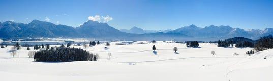 Breite Panoramalandschaft im Bayern mit Alpenbergen und im See im Winter stockbilder