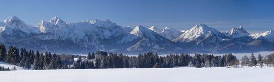 Breite Panoramalandschaft im Bayern mit Alpenbergen und im See im Winter stockbild