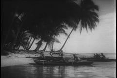 Breite Schusseingeborene, die auf Insel in den Kanus ankommen stock video