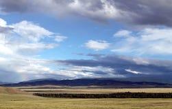 Breite Steppe mit gelbem Gras unter einem blauen Himmel mit Weiß bewölkt Sayan-Berge Sibirien Russland Lizenzfreies Stockbild