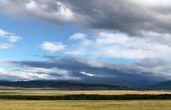 Breite Steppe mit gelbem Gras unter einem blauen Himmel mit Weiß bewölkt Sayan-Berge Sibirien Russland Lizenzfreie Stockbilder