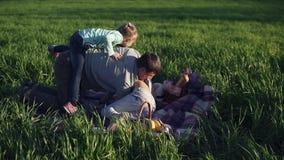 Breite Wiese mit grünem Gras Junger Vater und zwei Töchter haben Spaß zusammen Täuschen Sie herum Das jüngste hat stock video