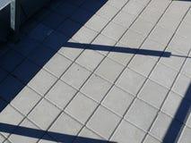 Breiten Sie Dach mit quadratischen Fliesen und Schatten auf Geländer aus Lizenzfreies Stockbild