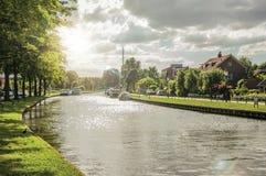Breiter Kanal von Bäumen gesäumt mit Häusern und Boote und Glanz des Sonnenuntergangs reflektierte sich im Wasser bei Weesp Stockbild