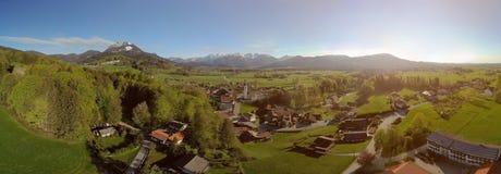 Breiter Panoramablick des alten bayerischen Dorfs und der Alpen lizenzfreies stockbild