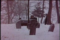 Breiter Schuss von den Männern, die Sarg durch Kirchhof im Winter tragen stock video footage