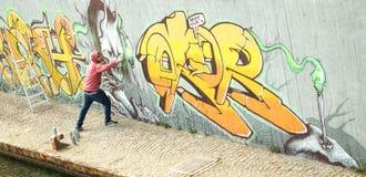 Breiter viewof Straßenkünstler, der bunte Graffiti auf generischem malt Lizenzfreies Stockfoto