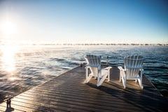 Breites Foto von Muskoka-Stühlen auf einem Dock mit dem Sonnensteigen und -nebel Lizenzfreie Stockbilder